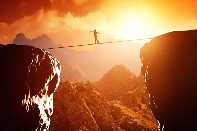 Man walking and balancing on rope over precipice in mountains