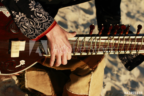 Picture of hand of a sitarist striking string