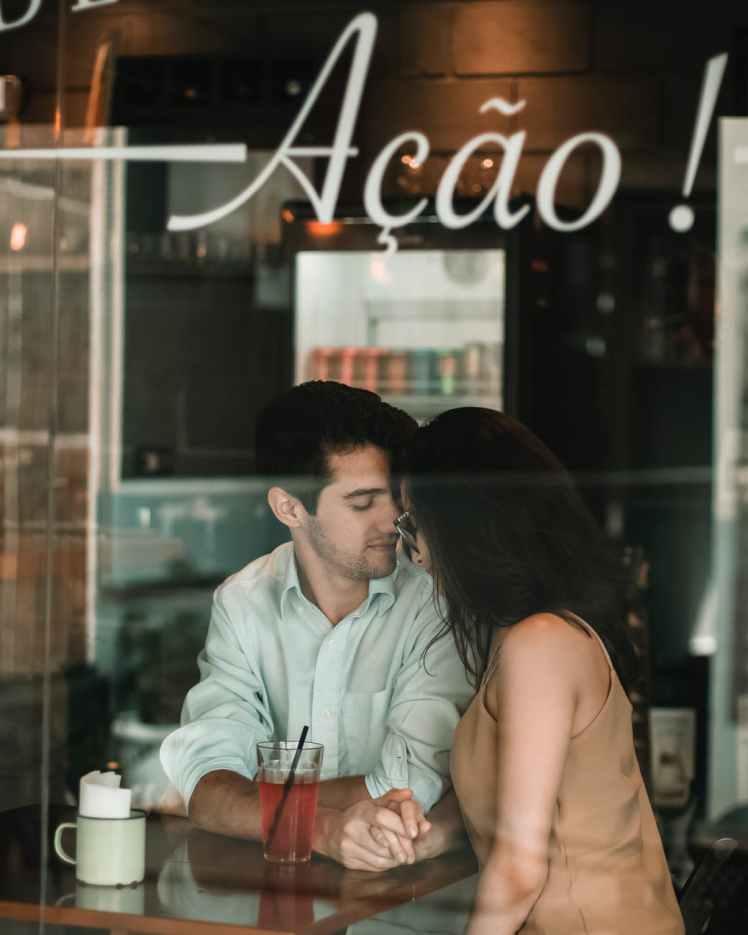 man in white dress shirt sitting beside woman in brown sleeveless top
